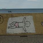 Graffiti na Bulwarze Nadmorskim w Gdyni. Niemowlę leży na kocyku. Obok japonki i pies zwinięty w kłębekwe