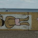 Graffiti na Bulwarze Nadmorskim w Gdyni. Facet z brodą i fajką leży i się opala