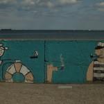 Graffiti na Bulwarze Nadmorskim w Gdyni. Marynarz, dziewczyna z kołem ratunkowym, pies pali fajkę i marynarz też