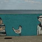 Graffiti na Bulwarze Nadmorskim w Gdyni. Marynarze a między nimi kura w marynarskiej czapce