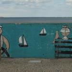 Graffiti na Bulwarze Nadmorskim w Gdyni. Dwóch marynarzy i dwie żaglówki . Na ramieniu jednego marynarza siedzi papuga a między nimi kura w marynarskiej czapce