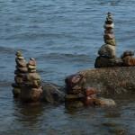 Na głazach zatopionych w morzu stoją trzy wieżyczki ułożone z kamyków położonych jeden na drugim