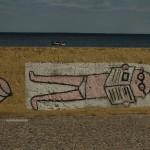 Graffiti na Bulwarze Nadmorskim w Gdyni. Leży facet w slipach i się opala czytając