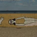Graffiti na Bulwarze Nadmorskim w Gdyni. Leży kobieta w okularach z pieskiem i się opala