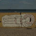 Graffiti na Bulwarze Nadmorskim w Gdyni. Kobieta w bikini opala się a obok leżą grabki i kileiszek