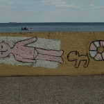 Graffiti na Bulwarze Nadmorskim w Gdyni. Chłopak leży i się opala obok kot i koło ratunkowe