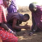 Masajowie rozniecają ogień, przez pocieranie patyków w kępce suchej trawy.