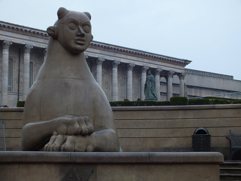 Birmingham, Victoria Square, Przy schodach prowadzących do Council House na Victoria Square w Birmingham  są dwa stwory, które zastępują lwy położone przed innymi schodami do ratuszów w Europie. Powyżej pomnik patronki placu – królowej Victorii [1819-1901] – na tle Town Hall zbudowanego na modłę Partenonu w Atenach. Zdjęcie zrobione w brytyjskiej mżawce, w innych warunkach na pewno bardziej by dech zapierało.