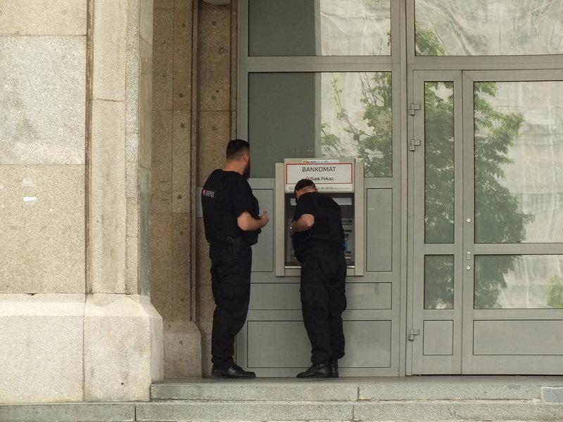Policjanci zaglądają do bankomatu czy nikt nie ukradł z niego pieniędzy