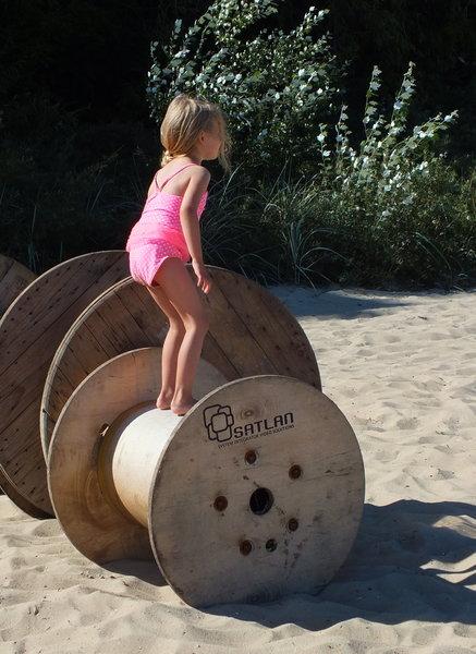 Dziewczynka skacze na szpuli po kablu elektrycznym na plaży w Gdyni Orłowo