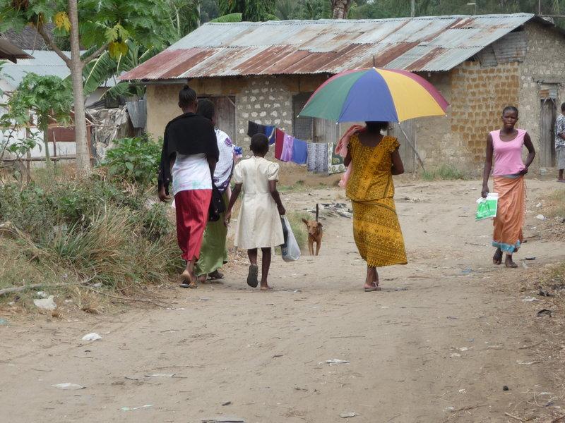 Kobiety wracają z zakupów w wiosce pod Mombasą w Kenii. Parasolem chronią przed słońcem najmniejsze dziecko