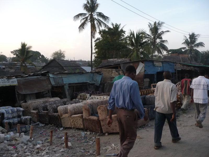 Sklep meblowy w Mombasie. Na ulicy stoją sofy. ZA nimi blaszane domki