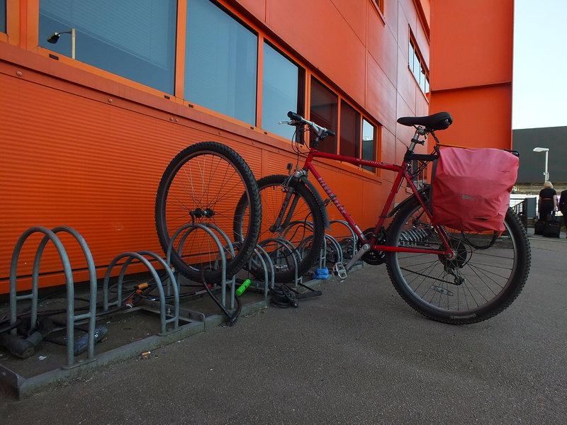 koło od roweru przypiete do stojaka przy lotnisku Londyn Luton. Rezszt e roweru ktoś ukradł. do st